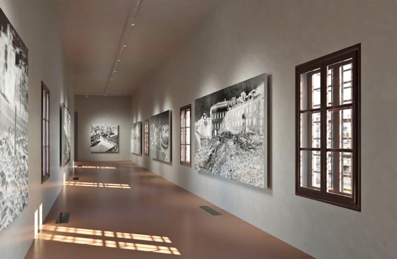 Fotografia dell'interno del corridoio Vasariano con le finestre sul lato destro da cui filtra la luce e dei quadri in bianco e nero appesi sulle pareti